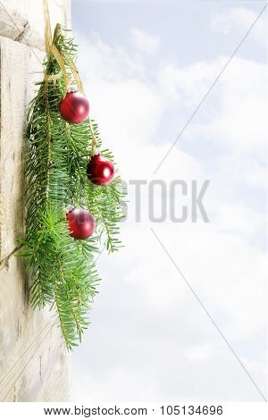 Fir Branches With Red Christmas Baubles On A Wooden Wall, Bright Sky In The Background