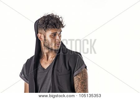 Handsome tough young man in dark hooded t-shirt isolated on white background, looking away to a side