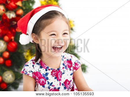 Happy Little Girl  With Santa  Hat In Front Of  Christmas Tree