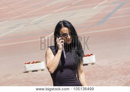 Caucasian Brunette In Sunglass Talking By Mobile