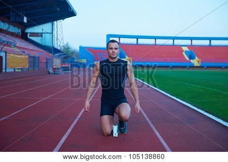 Sprinter leaving starting blocks on the running track. Explosive start.