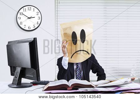 Businessperson With Cardboard Head Sitting In Office