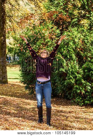 Woman enjoying the fall leaves