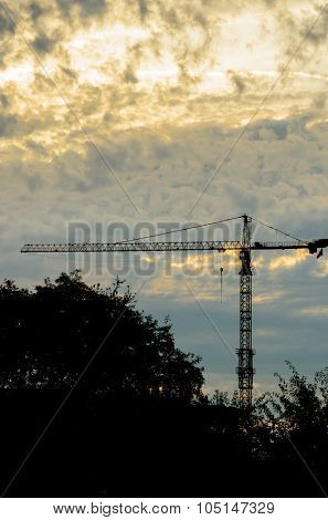 Construction site with cranes at sunset, sunrise, dawn time with the cranes as a silhouette. Vancouver, Canada. Vertical.