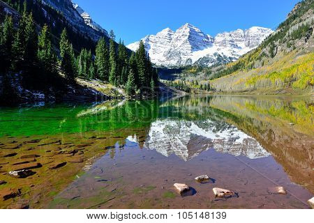 Maroon Bells During Foliage Season With Snow Covered Mountains And Yellow Aspen Reflecting In The La