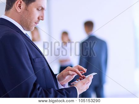 Portrait of young businessman using mobile in office with colleagues in the background