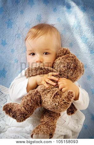 One year old baby holding a teddy bear