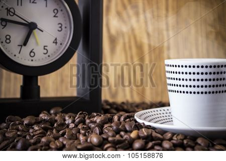 Cup Polka Dots And Clock Standing On Coffee Beans. Blur, Focus On Coffee Beans