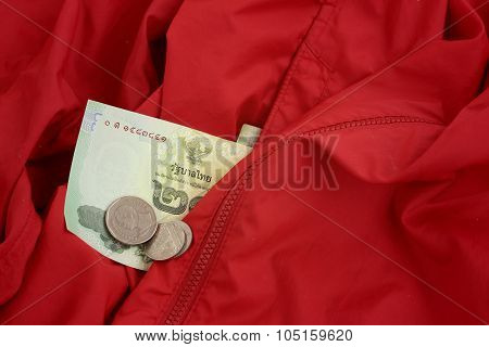 Thailand Baht Banknotes With Thailand Baht Coins On Red Shirt.