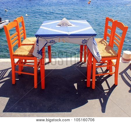 Tavern With Orange Wooden Chairs By The Sea Coast, Santorini