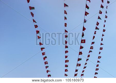 Bunting flags of Oman flying against blue sky. National day celebration of Oman.