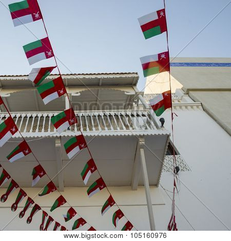 Small bunting flags of Oman hanging on an old omani house. National day celebration of Oman.