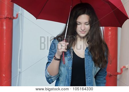 Street portrait of pedestrian girl with plain red umbrella in her arm