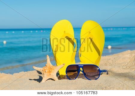 Sunny Positive Beach Vacation. Yellow Sandals, Sunglasses And Starfish On A Background Of The Sea