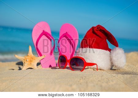 Happy  New Year Holidays And Merry Christmas At Sea. Sandals, Sunglasses And Santa Hat On Sandy Beac