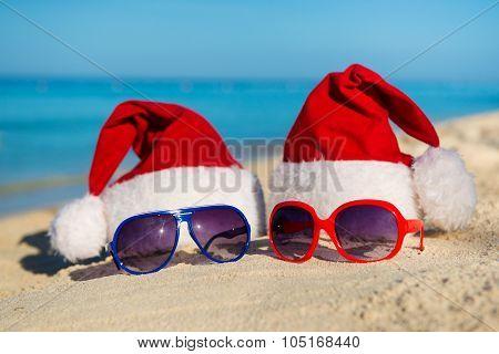 Christmas Holidays And Romantic New Year At Sea. Santa Hats And Sunglasses On Sandy Beach