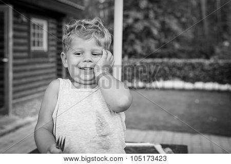 laughing boy child in black and white. he is trying to eat his meal with a fork but it just won't work