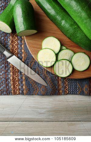 Fresh sliced zucchini on cutting board, on wooden background