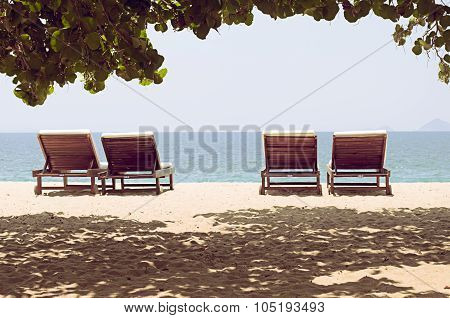Four Loungers On A Deserted Beach With A View Of The Horizon