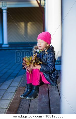 Autumn Concept - Daydreaming Little Girl With Yellow Leaves Sitting On The Porch