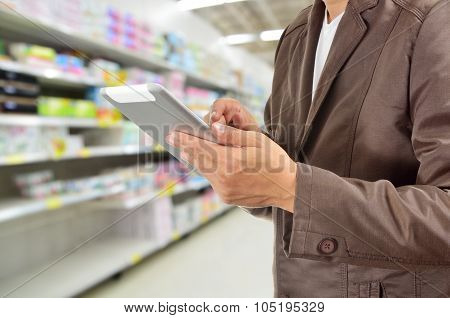 Young Man Hands Holding Tablet In Supermarket