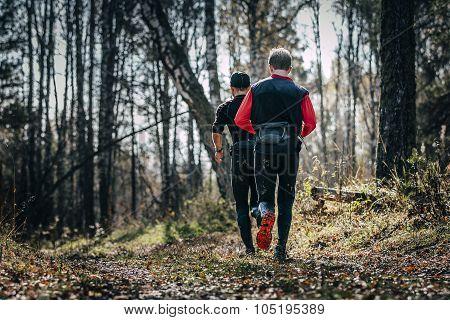 male runner running through forest