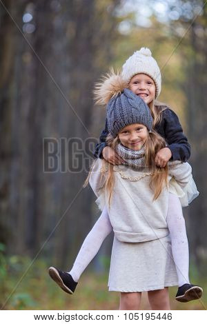 Little adorable sisters having fun at warm sunny autumn day