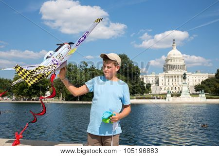 USA, WASHINGTON - AUG 26, 2014: Boy (with model release) and a kite is playing near United States Capitol at summer sunny day.