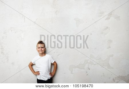 Young boy wearing white tshirt and smiling on the concrete wall background