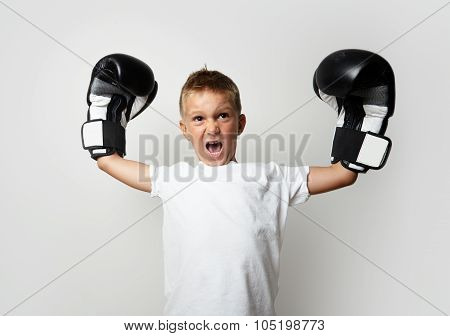 Little cute boy with boxing gloves celebrating his victory on the blank wall background