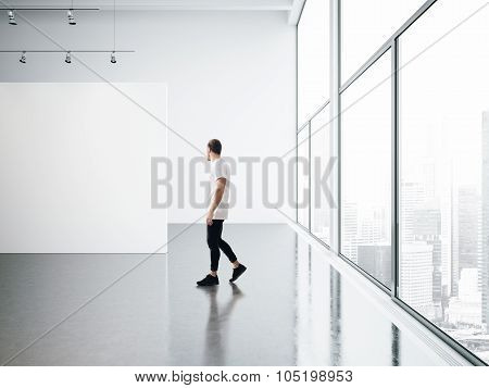 Empty gallery interior and walking young man