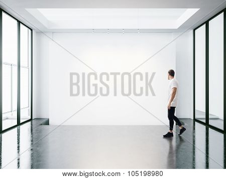 Panoramic windows in the gallery and young man walking