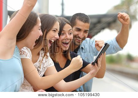 Four Euphoric Friends Watching A Tablet