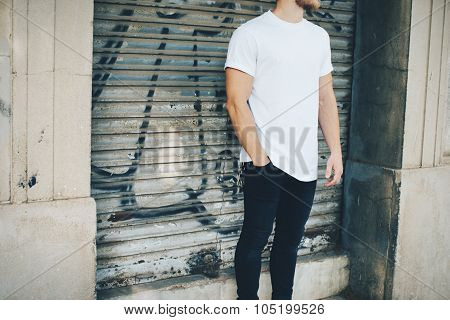 Bearded guy wearing white blank t-shirt and blue jeans, standing on the street