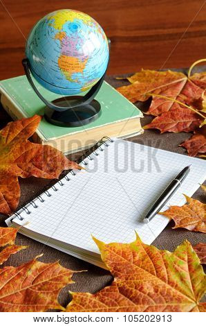 Old Book With Small Globe On It And Notebook With Ink Pen Near Maple Leaves On The Able
