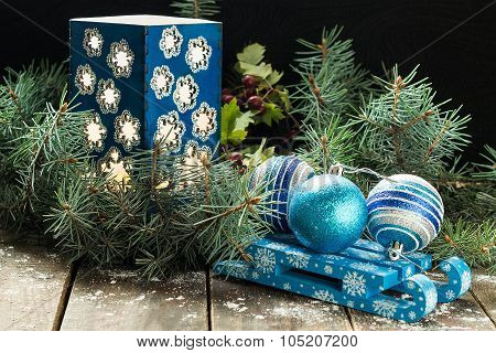 Blue Christmas Balls On A Sled And A Candlestick In The Branches Of Spruce