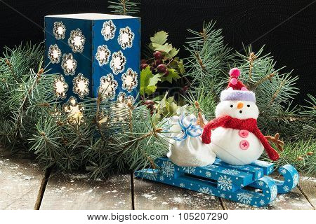 Candlestick In The Spruce Branches And A Snowman With Bag On A Sled