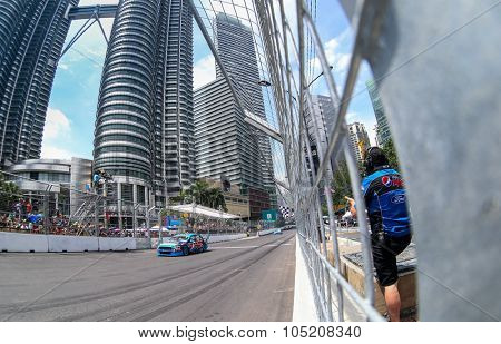 KUALA LUMPUR, MALAYSIA - AUGUST 09, 2015: Scott McLaughlin from the Volvo Polestar Racing team takes the checkered flag in the V8 Supercars Street Challenge at the 2015 Kuala Lumpur City Grand Prix.