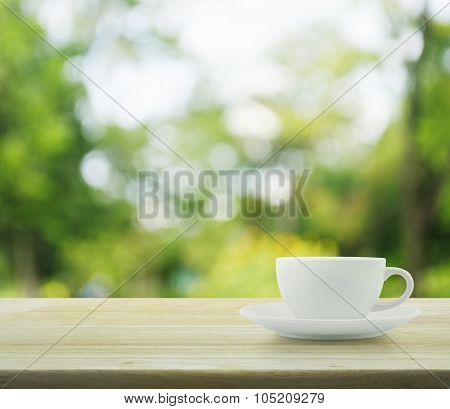 White Cup On Wooden Table Over Tree Bokeh Background