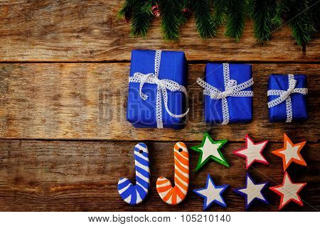 Wooden Background With Wooden Toys, Gifts And The Branches Of The Christmas Tree