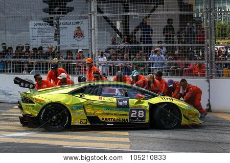 KUALA LUMPUR, MALAYSIA - AUGUST 09, 2015: Safety marshals push the Lamborghini car driven by Byron Tong to safety after it crashed in the race at the 2015 Kuala Lumpur City Grand Prix.