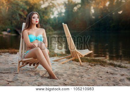Girl Is Sitting Deck Chair Beach Near The Lake.