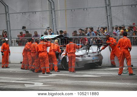 KUALA LUMPUR, MALAYSIA - AUGUST 09, 2015: Track safety marshals come to the aid of a car that crashed during the KL City GT Cup Race at the 2015 Kuala Lumpur City Grand Prix.