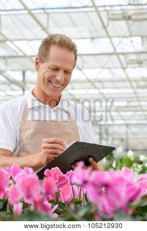 Professional florist workin gin the greenhouse
