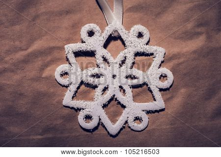 Christmas decoration, white snowflake from styrofoam  on paper, shot from above