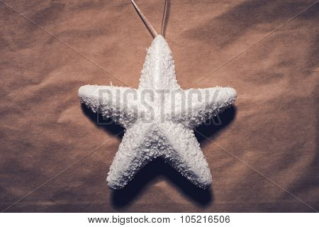 Christmas decoration, white star from styrofoam  on paper, shot from above