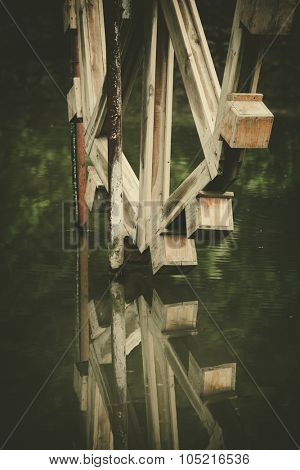 old wooden  watermill and a reflection in water closeup
