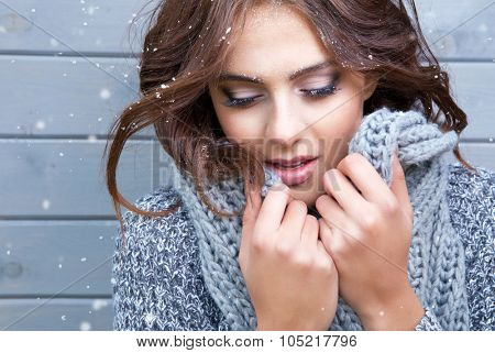 Beautiful natural young  brunette woman with eyes closed, wearing knitted scarf, covered with snow flakes. Snowing winter beauty concept.