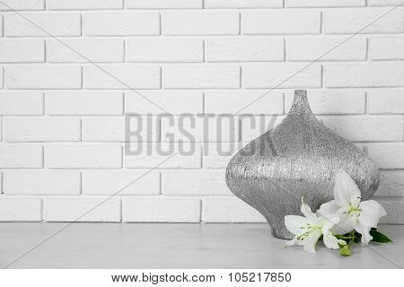 Beautiful vase and flowers on brick wall background