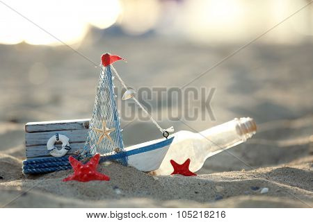 A little yacht with bottle and chest on the seashore